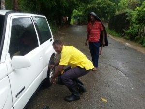 Steven Wallace (left) JAA Roadside assistance technician helps to inflate the tyres of a member of the public on the Mavis Bank main road as the team made their way to assist a member during preparations for hurricane Matthew.
